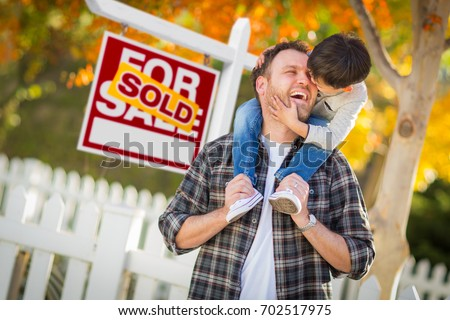 Young Mixed Race Chinese and Caucasian Father and Son In Front of Sold For Sale Real Estate Sign and Fall Yard.