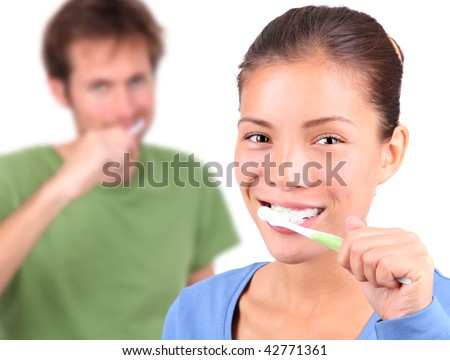 Young mixed race couple brushing teeth together on white background.