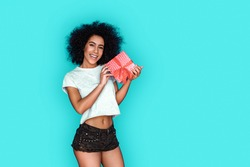 Young mixed race girl standing isolated on blue wall holding present box posing camera smiling playful