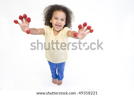Getty Images - Close up of woman biting raspberries on fingertips