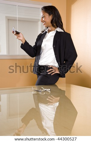 Young mixed-race Hispanic African-American woman in office boardroom texting on mobile phone
