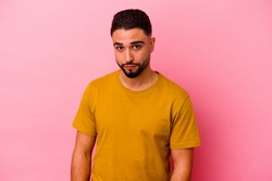 Young mixed race man isolated on pink background sad, serious face, feeling miserable and displeased.