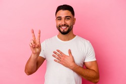 Young mixed race man isolated on pink background taking an oath, putting hand on chest.