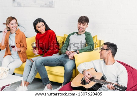 young mixed race man playing acoustic guitar for multiethnic friends