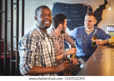 Young mixed race team of guys spending time together at sport bar, watching football game, drinking beer, afro guy looking at camera, empty space