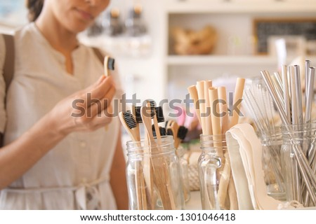 Young Mixed Race Woman Choosing Bamboo Eco Friendly Biodegradable Toothbrush in Zero Waste Shop. No plastic Conscious Minimalism Vegan Lifestyle. Reduce Reuse Recycle Concept.