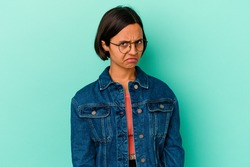 Young mixed race woman isolated on blue background sad, serious face, feeling miserable and displeased.