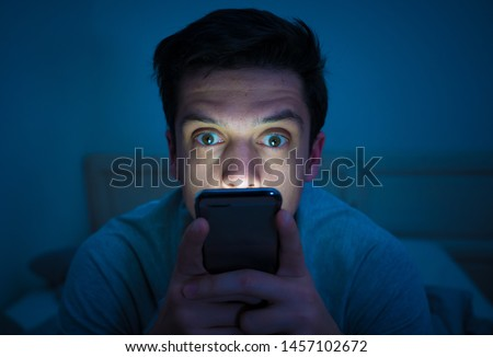 Young mobile phone addict man awake at night in bed using smartphone for chatting, flirting and sending text message. In communication, Internet addiction and Social media network abuse concept #1457102672