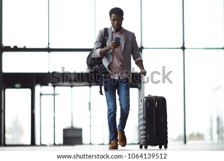 Young mobile traveler with smartphone, backpack and suitcase walking along airport and messaging or looking through online information