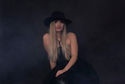 Young model in dark clothes and hat posing on black background.