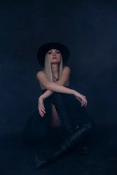 Young model in dark dress and hat posing on black background