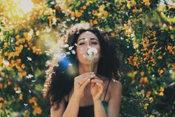 Young model look caucasian female with long dark curly hair wearing a black summer dress is blowing the dandelion at the camera while sitting on a blurred flowers background. Flare light.