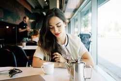 Young model look woman with long brown hair is sitting in a coffee shop during the brunch. Caucasian female with red lipstick on the lips is looking down while sitting at the table in the cafe.