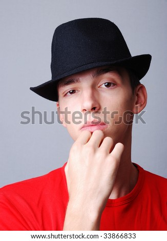 Young model with hat on head and thinking of expression