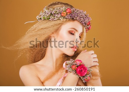 young model with wreath of spring flowers on her head. On yellow background
