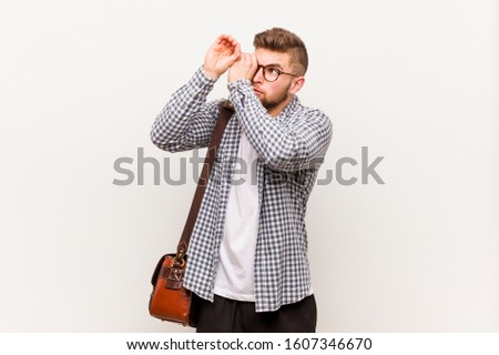 Young modern business man looking far away keeping him hand on forehead.