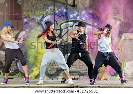 Young modern dancing group practice body jam in front colorful wall