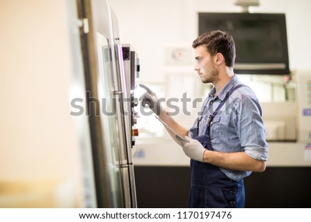 Young modern engineer with tablet standing in front of industrial machine and going to press one of buttons