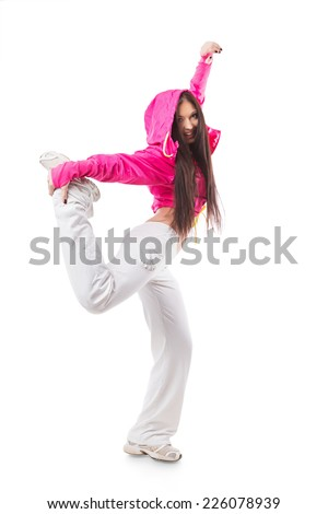 Young modern flexible hip-hop dance girl standing on one leg. Female in white sweatpants and a pink hoodie and sneakers standing on isolated white background.