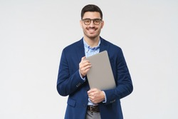Young modern male teacher holding closed laptop in hands, waiting for students, smiling confidently, isolated on gray background