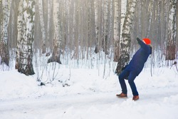 Young modern man slipped and lost his balance during a walk on a birch grove in winter. Freeze frame while jumping and waving his hands before falling to the snow.