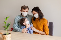 Young modern quarantined coronavirus family in medical masks. The call to stay home stop the pandemic. Self-isolation together is the solution. Care covid-19. mom dad son millennials