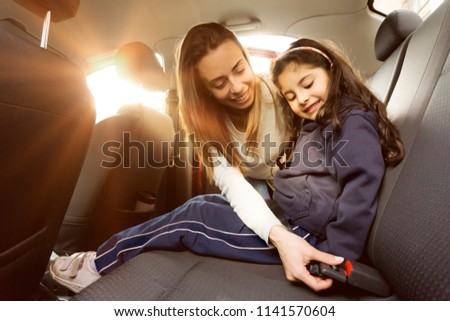 Young mom adjunsting her daughter seat belt