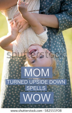"""Young mom and cheerful adorable blond girl playing, having fun together in park in summertime, mother playfully with little daughter. Photo with motivational text """"Mom turned upside down spells wow"""""""