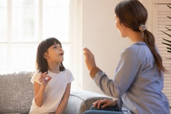 Young mom and little preschooler daughter at home learn sign language together, female nanny or teacher talk nonverbal with small disabled kid, practice sounds and signs making gestures