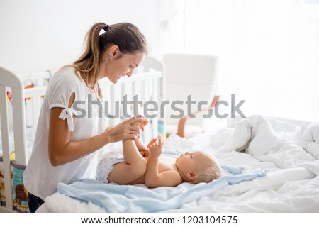 Young mom, changing baby diaper after bath in sunny bedroom Сток-фото ©