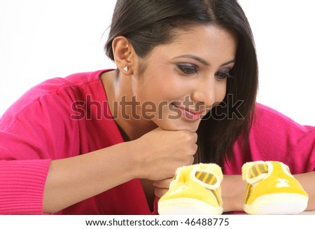 Young Mom feeling happy with small baby shoes