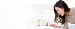 Young mom lying near the newborn baby while the infant is sleeping on the white bed. Asian mother looking and touching the baby's hand with love and care.