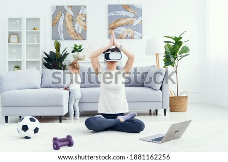 Young mom meditating in lotus yoga position using ar glasses while her daughter watches cartoons on background.