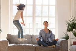 Young mom sit on couch at home meditating in lotus position, small daughter have fun jumping near, concentrated calm mother practice yoga relax on sofa ignore playful kid. Stress free concept