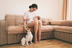 Young mom with her cute baby playing with jack russel terrier dog. Breastfeeding mother. Family and pet at home.