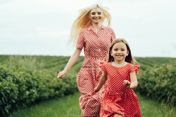 Young Mom with her Little Daughter Dressed Alike in Red Polka Dot Dress, Having Fun Time in Field Outside the City, Motherhood and Childhood Concept