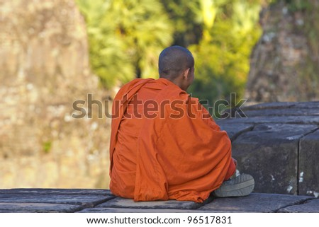 Young monk sits in the ruins of Angkor Wat