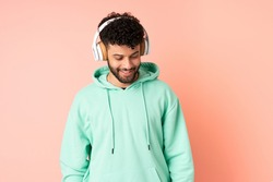 Young Moroccan man isolated on pink background listening music