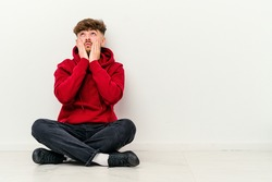 Young Moroccan man sitting on the floor isolated on white background whining and crying disconsolately.