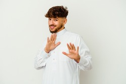 Young Moroccan man wearing a typical arab clothes isolated on white background rejecting someone showing a gesture of disgust.