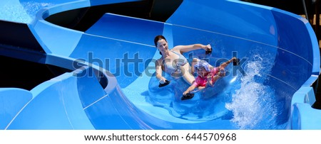 Young mother (age 30) and child (girl age 04) having fun in water park. Summer family vacation holiday concept. Real people. Copy space