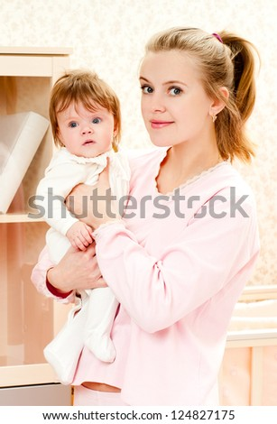 young mother and baby daughter at home