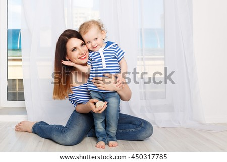 Young mother and baby daughter hugging. Mother and daughter dressed in a striped t-shirt. Mother holding a seashell. Family joy