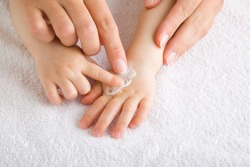 Young mother and baby fingers together applying moisturizing cream on baby hand on white towel. Care about children clean and soft body skin. Front view. Closeup.