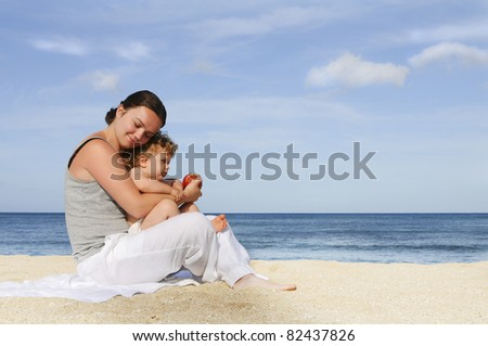Young mother and baby girl sitting on the tropical beach