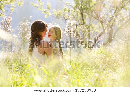Young mother and child daughter together, hugging and joyfully laughing while relaxing in a golden field of sunshine and spring flowers while on a summer holiday. Family outdoors lifestyle.