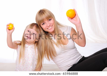Young mother and child spend time together. kept in the hands of oranges
