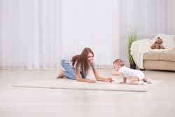 Young mother and cute baby playing on floor at home
