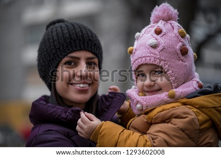 Young mother and cute girl child outdoors portrait. Winter photo. Cold outside people with winter hats