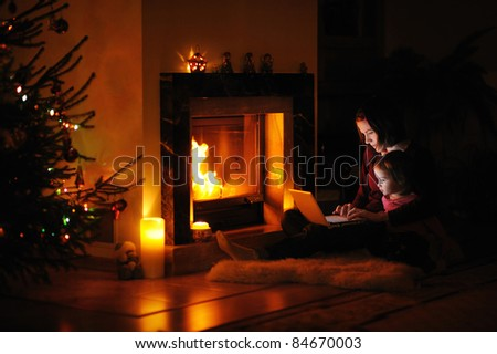 Young mother and daughter by a fireplace on Christmas